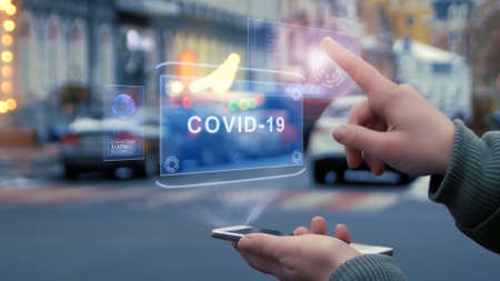 Female hands on the street interact with a HUD hologram with text COVID-19. Woman uses the holographic technology of the future in the smartphone screen on the background of the evening city