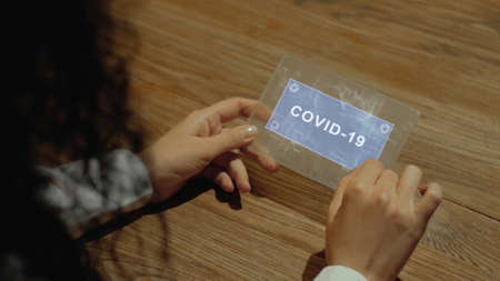 Unrecognizable woman working on a futuristic tablet with a hologram text COVID-19. Womens hands with future holographic technology at a wooden table
