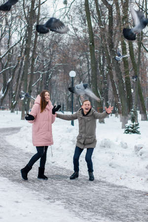 Happy young couple scare pigeons of winter travelers. Woman and man have fun in a winter snowy park. Young couple having fun in the park during the cold season