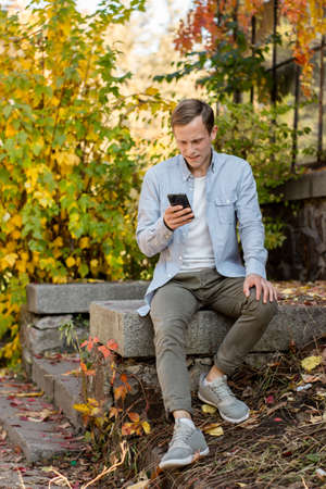 Guy with a phone in casual clothes in the autumn park. Successful student in blue shirt is enjoying life Imagens