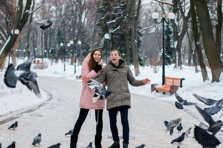 Happy young Woman and man scare pigeons. Couple have fun in a winter snowy park. Young couple having fun in the park during the cold season