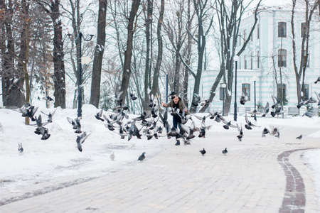 Happy young man scares pigeons. Guy have fun in a winter snowy park during the cold season Imagens