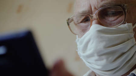 Sad elderly man in isolation at home wearing a handmade virus protection mask uses phone close up. Reading news from a smartphone in a home interior. Old man with glasses stays in quarantine at home Imagens