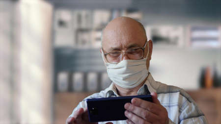 Elderly man in isolation at home wearing a handmade virus protection mask uses phone. Reading news from a smartphone in a home interior. Old man with glasses stays in quarantine at home