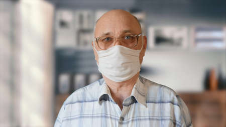 Elderly man in handmade homemade protective mask indoors. The concept of health and safety of old people during the pandemic of the coronavirus COVID-19