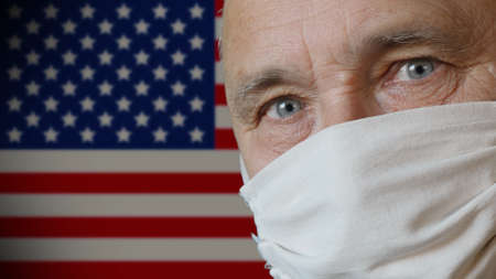 Scared elderly man in a handmade improvised protective mask on copy space USA flag background. Health and safety concept for older people during the COVID-19 coronavirus pandemic in America