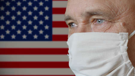 Elderly man in a handmade improvised protective mask on copy space USA flag background. Health and safety concept for older people during the COVID-19 coronavirus pandemic in America