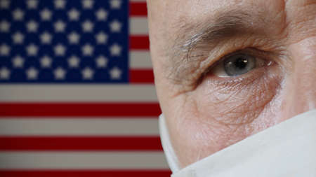 Half face of elderly man in protective mask close-up on copy space background of USA flag. Health and safety concept for older people during COVID-19 coronavirus pandemic in America Imagens