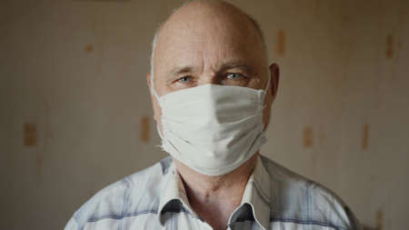 Portrait of an elderly man in handmade homemade protective mask indoors. The concept of health and safety of old people during the pandemic of the coronavirus COVID-19