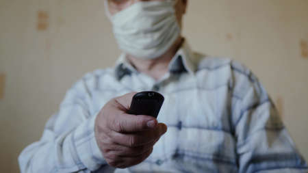 Unrecognizable old man in a protective face mask switches channels using the remote control. Quarantine retirement during a coronovirus pandemic