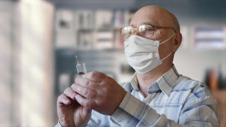 Health and medical concept of the elderly. Old man in glasses and protective mask holds a syringe and pour the substance