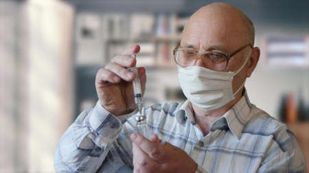 Old man in glasses and protective mask holds a syringe and pour the substance into the vaccine bottle. Health and medical concept of the elderly