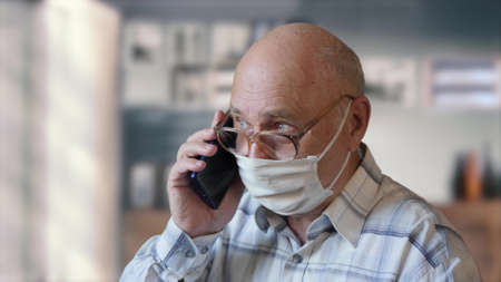 An elderly man in isolation at home in glasses and a handmade virus protection mask speaks on the phone. A conversation on a smartphone in the home interior. Old man is in quarantine Imagens