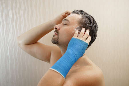 Handsome middle-aged man takes a shower with his hand wrapped in a plaster cast, washes his hair in the bathroom. Broken wrist in modern blue waterproof bandage Imagens