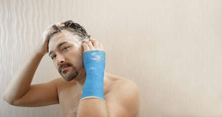 Handsome middle-aged man takes a shower with his hand wrapped in blue waterproof bandage, washes his hair in the bathroom copy space. Broken wrist in modern a plaster cast Imagens