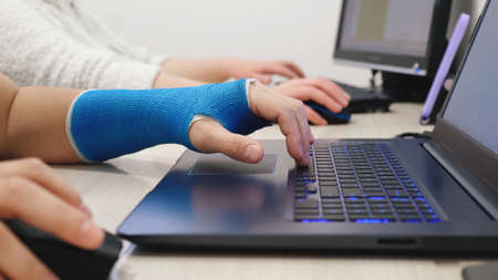 Male hand wrapped in fiberglass plaster cast typing on a laptop computer keyboard. Manager with one broken wrist works the Internet in office Imagens