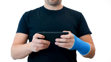 Unrecognizable middle-aged bearded man in a black T-shirt with a broken wrist plays games on the phone against a white background. Male hand, wrapped in a fiberglass plaster cast, uses a mobile phone