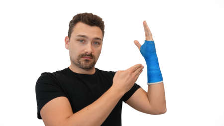 Handsome middle-aged bearded man in a black T-shirt shows his hand wrapped in a plaster cast on a white background. Broken wrist in modern blue waterproof bandage Imagens