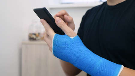 Male hand, wrapped in a  plaster cast, scrolls through a touchscreen on a mobile phone. Unrecognizable man in black t-shirt with broken wrist surfs the internet at home