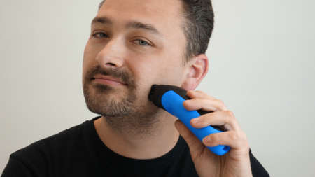 Handsome middle-aged man shaves his cheek with an electric safety razor. Shaving the beard on the face. Male hand smoothly shaves stubble with shaving machine on bright background