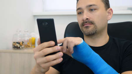 Handsome middle-aged man in black t-shirt with broken wrist surfs the internet at home. Male hand, wrapped in a fiberglass plaster cast, uses a touchscreen on a mobile phone