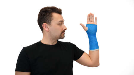 Handsome middle-aged bearded man in a black T-shirt looks at his hand wrapped in a plaster cast on a white background. Broken wrist in modern blue waterproof bandage