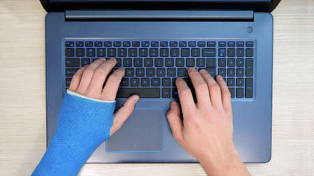 Top view of hands typing on a laptop computer on a keyboard, one hand wrapped in fiberglass plaster cast. A freelancer with one broken wrist works the Internet at home