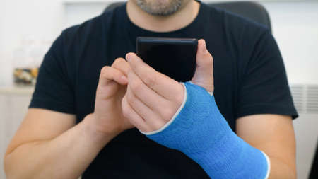 Unrecognizable bearded middle-aged man in black t-shirt with broken wrist surfs the internet at home. Male hand, wrapped in a  plaster cast, uses a touchscreen on a mobile phone