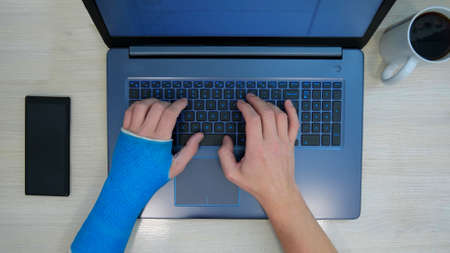 Hands typing on a laptop computer on a keyboard, one hand wrapped in  plaster cast. Top view of freelancer with one broken wrist works the Internet at home