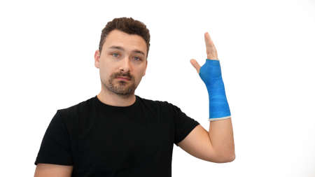 Broken wrist in modern blue waterproof bandage. Handsome middle-aged bearded man in a black T-shirt shows his hand wrapped in a plaster cast on a white background
