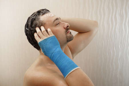Broken wrist in modern blue waterproof bandage. Handsome middle-aged man takes a shower with his hand wrapped in a plaster cast, washes his hair in the bathroom