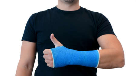 Unrecognizable man in a black T-shirt shows thumbs up and hand wrapped in a plaster cast on a white background. Broken wrist in modern blue waterproof bandage Imagens