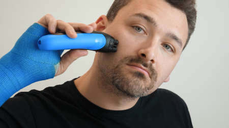 Man with hand wrapped in fiberglass plaster cast shaves his cheek with an electric safety razor. Male hand in blue waterproof bandage shaves stubble with a razor on a bright background