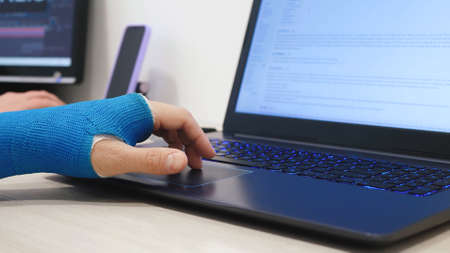 Male hand wrapped in fiberglass plaster cast scrolls on a laptop touchpad. Manager with broken wrist works the Internet in office