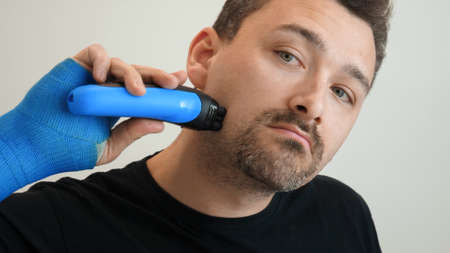 Man shaves his cheek with electric razor