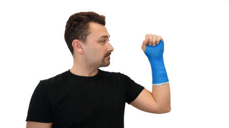 Man looks at plaster cast on white background
