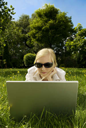 young woman working outside on computer