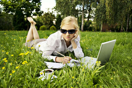 young woman working outside on computer and drinking coffee photo