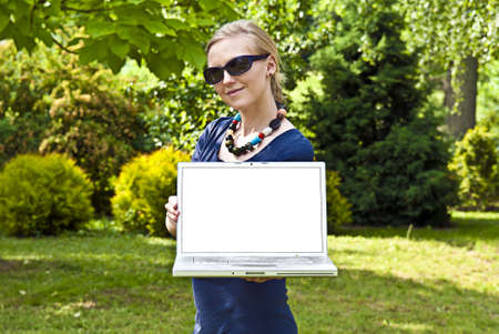 Young blonde woman with computer in the garden.Giving computer, giving internet. Stock Photo
