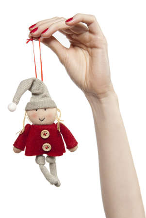 Studio photo of womanshands playing with puppet. Dwarf on the white background.