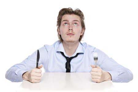 Junger Mann ist hungrig. Studioaufnahme des hungrigen Menschen, isoliert auf weiss. Standard-Bild