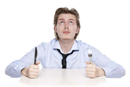 Young man is hungry. Studio shot of hungry man, isolated on white. photo