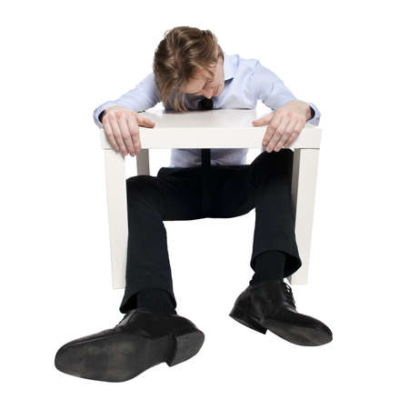 woeful: Young businessman, office worker or student sleeping at funny small table. Studio photo of sleeping man. Isolated.