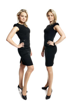 Portrait of two attractive young women in a black dress looking at camera. Stock Photo