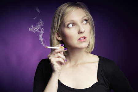 Young woman smoking cigarette  Purple background  photo