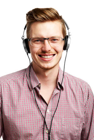 Young man listens to music and smiles with headphones  photo