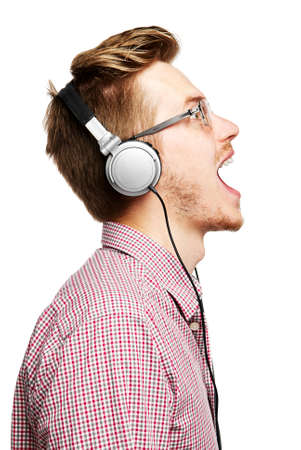 Young man listening to music and singing with headphones  Isolated on white