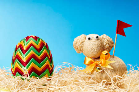 pasen schaap: Easter egg and easter lamb with red flag and yellow bow on the blue background.