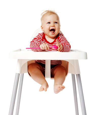 Baby sitting on chair and waiting for dinner. Isolated on white Background.