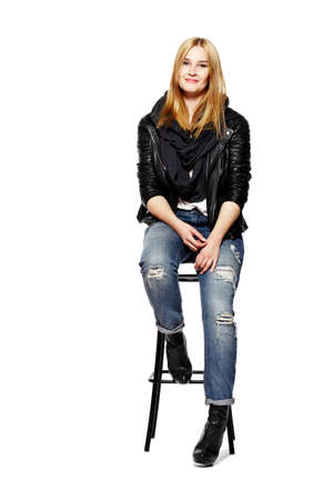 Young blonde woman sitting on high stool. Isolated on white background.